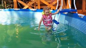 Mała dziewczynka pływa w basenie