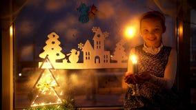 Mała dziewczynka patrzeje świeczkę i marzy Nowy Rok dekoracj choinka zdjęcie wideo