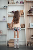 Mała dziewczynka patrzeje dla książki w bibliotece; Obraz Stock