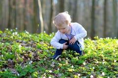 Mała dziewczynka patrzeje dla Wielkanocnych jajek w lesie Fotografia Royalty Free