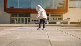 Mała dziewczynka patrzeje jej sneakers outdoors z hoodie obrazy royalty free