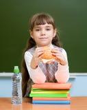 Mała dziewczynka patrzeje kamerę w sala lekcyjnej z hamburgerem Fotografia Stock