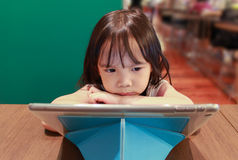 Mała dziewczynka patrzeje pastylkę na społeczeństwie Obraz Royalty Free