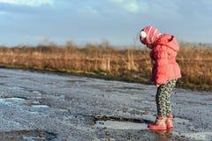 Mała dziewczynka patrzeje w kałużę, dzieci, zabawa, niezapomniani momenty, zabawa z ojcem, życie w wiosce, światło słoneczne Poję Obraz Stock
