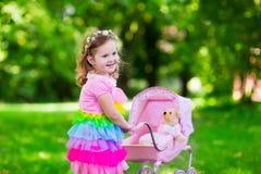 Mała dziewczynka pcha zabawkarskiego stoller z lalą Obrazy Royalty Free
