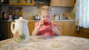 Mała dziewczynka pije sok i ono uśmiecha się zbiory