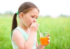 Mała dziewczynka pije sok pomarańczowego Zdjęcie Royalty Free