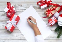 Mała dziewczynka pisze liście Święty Mikołaj fotografia stock