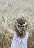 Mała dziewczynka pobyt z wiankiem banatka na jej głowie i trzymać bukiet banatka widok z powrotem zdjęcie royalty free