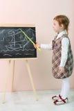 Mała dziewczynka pokazuje żółtym pointeru statkiem przy chalkboard fotografia stock