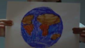 Mała dziewczynka pokazuje w kamera rysunek ziemia, oprócz planeta programa, jedność zbiory