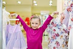 Mała dziewczynka pokazuje wieszaki z spódnicą i bluzką obraz royalty free