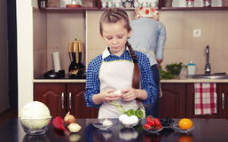 Mała dziewczynka pomaga jej matki gotować zdjęcia stock