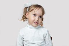 Mała dziewczynka przechylał jej głowę na jej stronie Zdjęcia Royalty Free