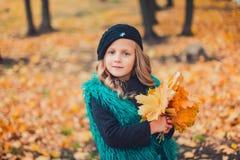 Mała dziewczynka przy jesieni mienia liśćmi Mała dziewczynka w brown berecie w jesień parku zdjęcie stock