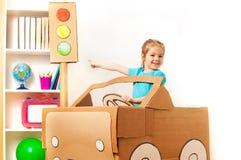 Mała dziewczynka przy kołem handmade kartonowy samochód Obrazy Royalty Free