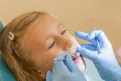 Mała dziewczynka przy przyjęciem w dentist& x27; s biuro Małej dziewczynki obsiadanie w krześle blisko dentysty po stomatologiczn zdjęcia royalty free