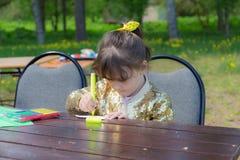 Mała dziewczynka przy stołem Zdjęcia Royalty Free