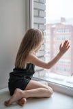 Mała dziewczynka przyglądająca out nadokienny czekanie Obrazy Royalty Free