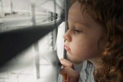 Mała dziewczynka przyglądająca out okno Obraz Royalty Free