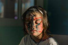 mała dziewczynka przyglądający motyl malował twarzy obsiadanie i marzyć z zamkniętymi oczami zaświecał słońce promieniami w ciemn Fotografia Royalty Free