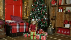 Mała dziewczynka przyglądający prezent pod choinką Zdjęcie Stock