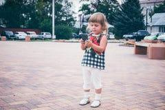 Mała dziewczynka przyglądający telefon komórkowy Zdjęcie Stock