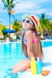 Mała dziewczynka relaksuje w basenie Zbliżenie butelka słońce śmietanka na krawędzi pływackiego basenu fotografia royalty free