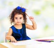 Mała dziewczynka remisy przy stołem z ołówkami Fotografia Stock