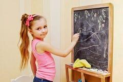Mała dziewczynka remisy z kredą na blackboard zdjęcia royalty free