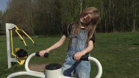 Mała dziewczynka robi ćwiczeniom dla nóg na stażowej maszynie w parku zdjęcie wideo