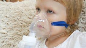 Mała dziewczynka robi inhalacji z nebulizer w domu i patrzeje TV dziecko astmy inhalatoru nebulizer inhalacyjna kontrpara zdjęcie wideo