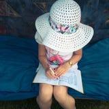 Mała dziewczynka robi jej pracie domowej w ogródzie Zdjęcie Stock