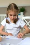 Mała dziewczynka robi papierowi heblować obraz stock