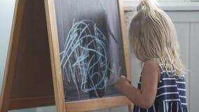 Mała dziewczynka rysuje błękit kredę na blackboard zbiory