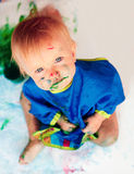 Mała dziewczynka rysuje barwionego farby obsiadanie na Obrazy Royalty Free