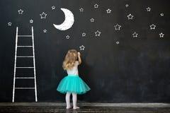 mała dziewczynka rysuje księżyc i gra główna rolę na blackboard Obraz Royalty Free