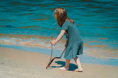 Mała dziewczynka rysuje na piasku przy plażą Fotografia Royalty Free