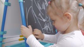 Mała dziewczynka rysuje z kredą na blackboard w pepinierze Mama siedzi obok ona i podziwia dziecka zbiory wideo