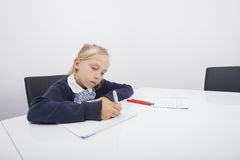 Mała dziewczynka rysunek na papierze z odczuwanym porady piórem przy stołem Fotografia Stock