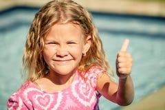 Mała dziewczynka siedzi blisko pływackiego basenu Zdjęcia Stock