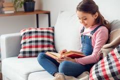 Mała dziewczynka siedzi czytelniczą książkę excited w domu obrazy royalty free