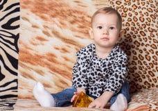 Mała dziewczynka siedzi na żyłkowanej pasiastej leżance Obraz Royalty Free