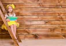 Mała dziewczynka siedzi na drabinie z stertą książki Zdjęcie Royalty Free