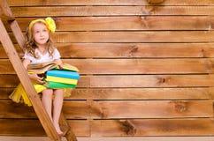 Mała dziewczynka siedzi na drabinie z stertą książki Obrazy Royalty Free