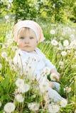 Mała dziewczynka siedzi w dandelions Zdjęcia Stock