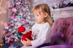 Mała dziewczynka siedzi na kanapie i chwyty bawją się Święty Mikołaj w ręce Zdjęcie Stock