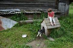 mała dziewczynka siedzi na małym dog& x27; s budka zdjęcie royalty free