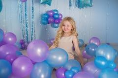 Mała dziewczynka siedzi na podłoga studio z mnóstwo kolorów balonami Obraz Royalty Free