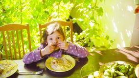 Mała dziewczynka siedzi przy stołem i je makaron zbiory